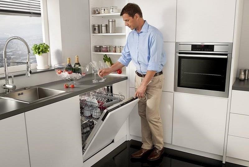 Мужчина загружает посудомойку